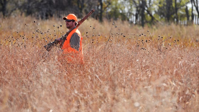Tyler Garry walks through a slough while hunting for pheasants on opening day in October on the family farm near Salem.