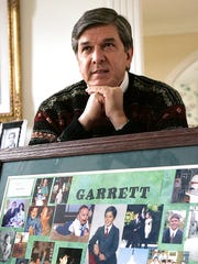 In this March 18, 2006 file photo, Sen. Gordon Smith, R-Ore., sits at his Pendleton, Ore., home behind a photo collage of his son, Garrett, who took his life in 2003. His suicide led to the creation of a federal grant, which has awarded $76 million for prevention programs to more than 230 colleges since 2005, on top of millions that institutions have spent on their own.