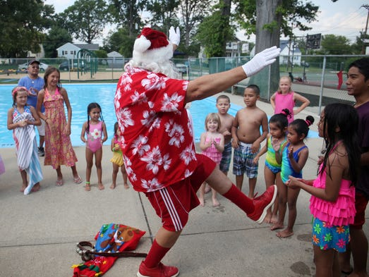 Santa, portrayed by Raritan Borough assistant recreation director Bob Andreychak, visits children at the Frelinghuysen Park Pool to celebrate Christmas in July, Thursday, July 31, 2014, in Raritan Borough, NJ.  Photo by Jason Towlen