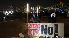 Anti-Olympic activists hold a sign as the illuminated Olympic rings are visible in the distance Friday, Jan. 24, 2020, in the Odaiba district of Tokyo. Tokyo put on a flashy fireworks display on Friday to mark the 6-months-to-go milestone for this summer's Olympics. (AP Photo/Jae C. Hong)