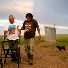 Johnathan Colorado assists his father, Charley Colorado, 87, who suffers from pulmonary fibrosis, in walking back from the outhouse back to inside their home outside of Gray Mountain on the Navajo Reservation. Because of the pulmonary fibrosis Charley has trouble walking which is complicated by the fact that the family has no indoor plumbing.