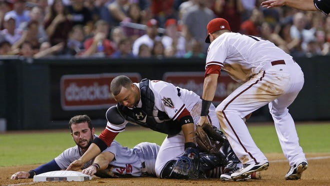 St. Louis Cardinals baserunner Greg Garcia (left) and Diamondbacks catcher Welington Castillo (center) collide during a play at third base on Monday night at Chase Field. Garcia slid in safely after Castillo failed to catch the ball for the tag.