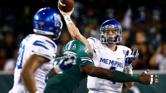University of Memphis quarterback Riley Ferguson (right) looks to make a pass against the Tulane University defense during first quarter action at Yulman Stadium in New Orleans. Ferguson  completed 21 passes on 34 attempts for 236 yards.