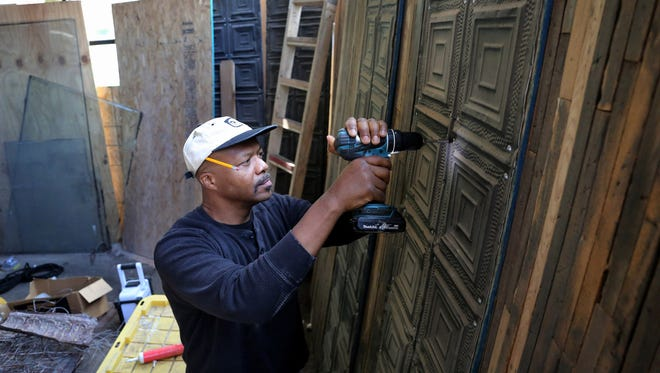 Tsadakeeyah Emmanuel works on tin tiles to be used on the ceiling of his new vegan catering space in Chicago's South Shore neighborhood. Small business owners' view of the economy is surging and giving them an incentive to hire, according to surveys by two small business groups.