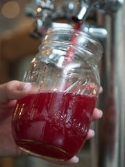 Kombucha Happy Hour is a popular drop-in in Westmont. The BYOB event also includes options off the food menu. Kelsey Coyne pours an Orange Hibiscus Kombucha at Heart Beet Kitchen.