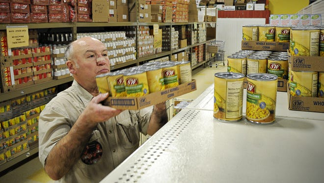 Volunteer Al Brixius stocks cans of corn on the shelves at the Catholic Charities food shelf. The new Rotaract chapter is hosting a food drive for the shelf.