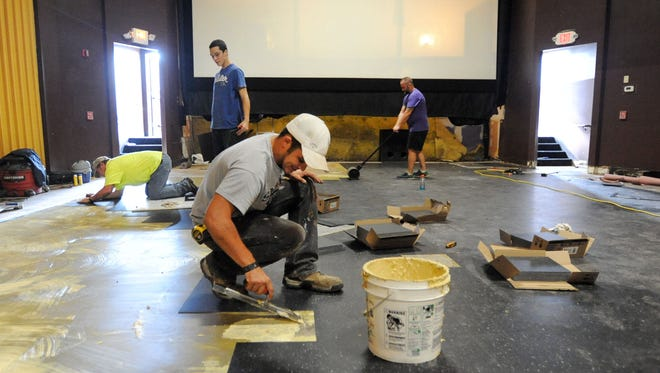 Workers from Miracle Floor Covering, Marion, install a new floor in one of the theaters in the Centre Cinemas 7 at the Marion Centre mall. The cinema is open and undergoing renovations and upgrades under the new owners, Republic Theatres Group.