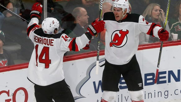 New Jersey Devils' John Moore, right, and Adam Henrique