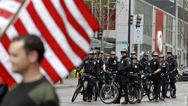 Seattle police officers on bicycles wait to follow an anti-war march by veterans during a May Day demonstration Monday, May 1, 2017, in Seattle.