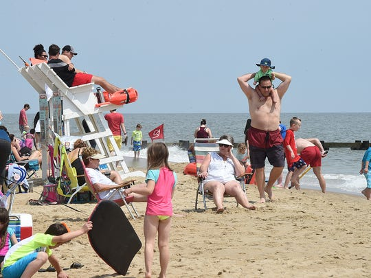 Cool weather keeps visitors out of the water in Rehoboth Beach as the Memorial Day weekend starts the summer season with a large crowd on the beach and boardwalk on Sunday, May 28, 2017.
