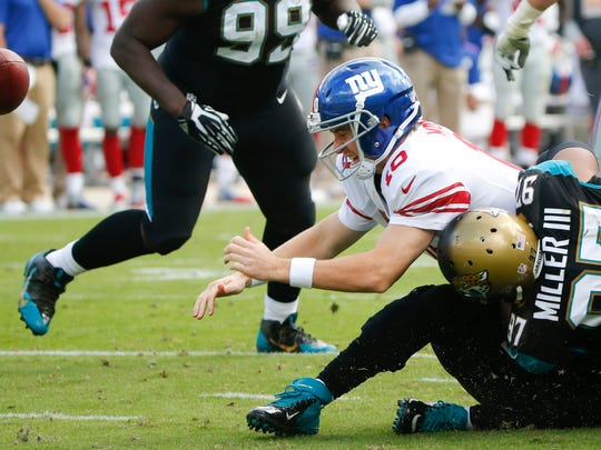 New York Giants quarterback Eli Manning (10) fumbles the ball as he is hit by Jacksonville Jaguars defensive tackle Roy Miller (97) during the second half of Sunday's game in Jacksonville, Fla. The ball bounced in the end zone and was recovered by Jacksonville for a touchdown.