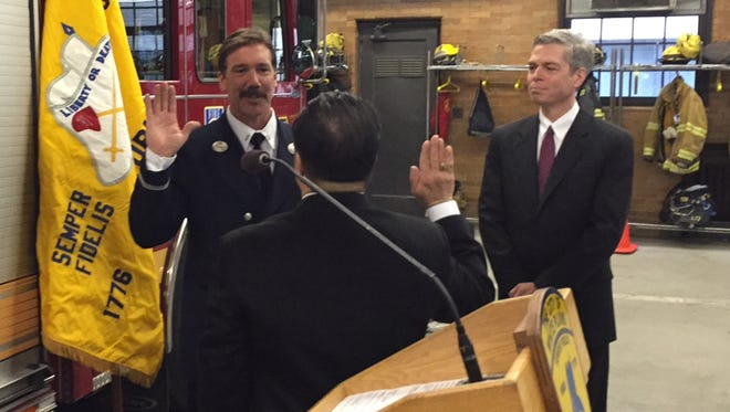 Leonard Bonadies takes the oath of office as White Plains deputy fire chief from Public Safety Commissioner David Chong (back to camera), March 20, 2015. Mayor Thomas Roach is at right.
