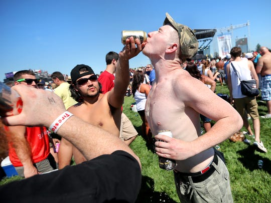 Shane Cail of Cambridge City, Indiana shoots a beer with help from Edwin Bruno, left, as he celebrates his 21st birthday during the Sublime concert during Carb Day at the Indianapolis Motor Speedway on Friday, May 23, 2014.