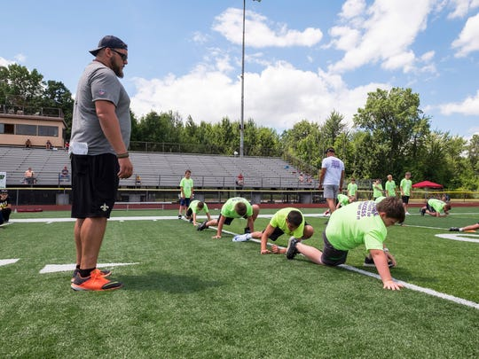Former Detroit Lions offensive lineman and St. Clair graduate Tim Lelito, left, watches group of kids warmup Wednesday, July 18, 2018, at the Lelito Legacy football camp at East China Stadium.