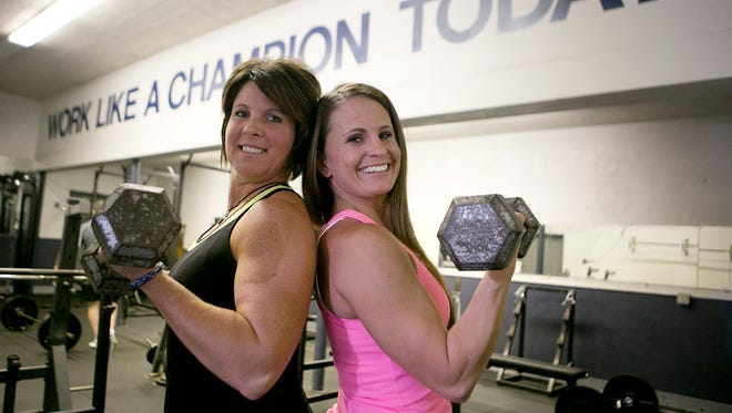 Katrina Oluszczyk-Freek, left, and Becky Holland, right pose in the weight room at Columbus Catholic High School in Marshfield, Wednesday, July 9, 2014.