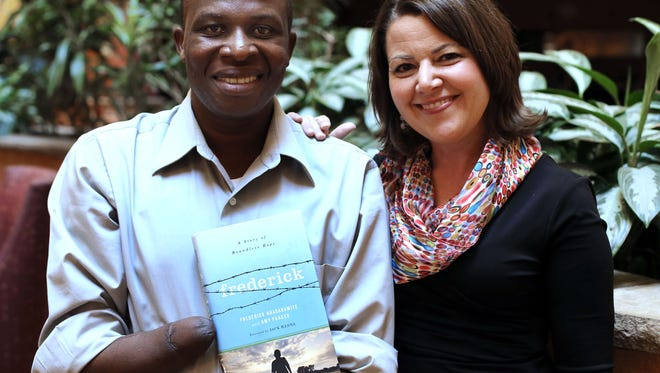 Frederick Ndabaramiye holds a copy of his book, 'Frederick: A Story of Boundless Hope,' which was coauthored by local author Amy Parker. Ndabaramiye survived having his hands being chopped off by a machete-wielding rebel group four years after the 100-day Rwandan genocide.