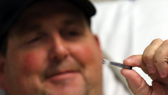 Michael Davis, 56, holds up a cardiac monitor identical to one that was inserted into his chest. The manufacturer of the monitor, Minneapolis-based Medtronic, is merging with an Ireland-based company in a 'tax inversion' that will cost Minnesota tax revenue.