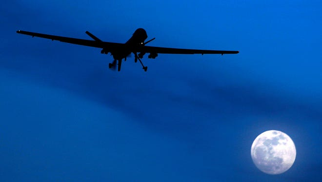 An unmanned U.S. Predator drone flies over Kandahar Air Field, southern Afghanistan, on a moon-lit night.