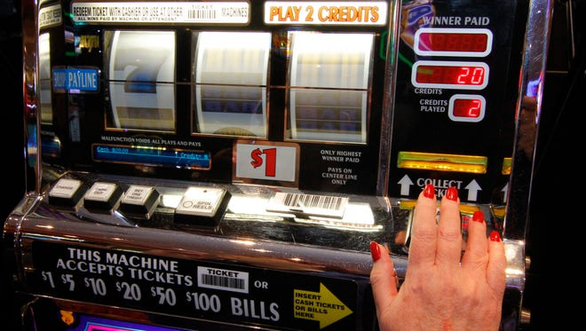 A gamer takes her spin on a slot machine at a casino.