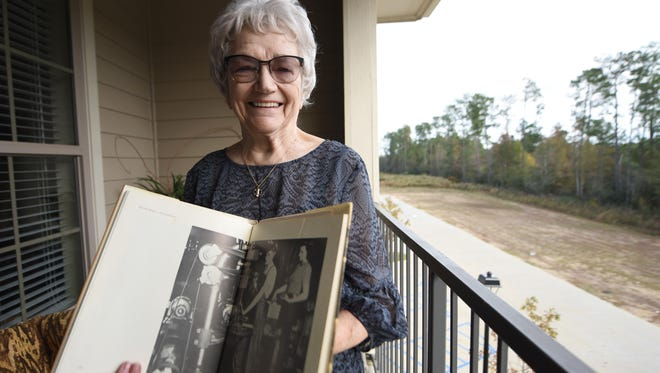 Edith Massey, 91, of Hattiesburg holds up a photo of her making threads in the 20mm shells at Komp Equipment during World War II. Massey received the Army-Navy E Award for her hard work at the plant.
