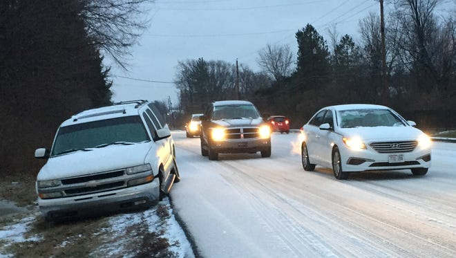 Cars drive north past a car that appears to have slid off the road in the 8200 block of Michigan Road after a winter storm hit Indianapolis, Friday, Jan. 12, 2018.
