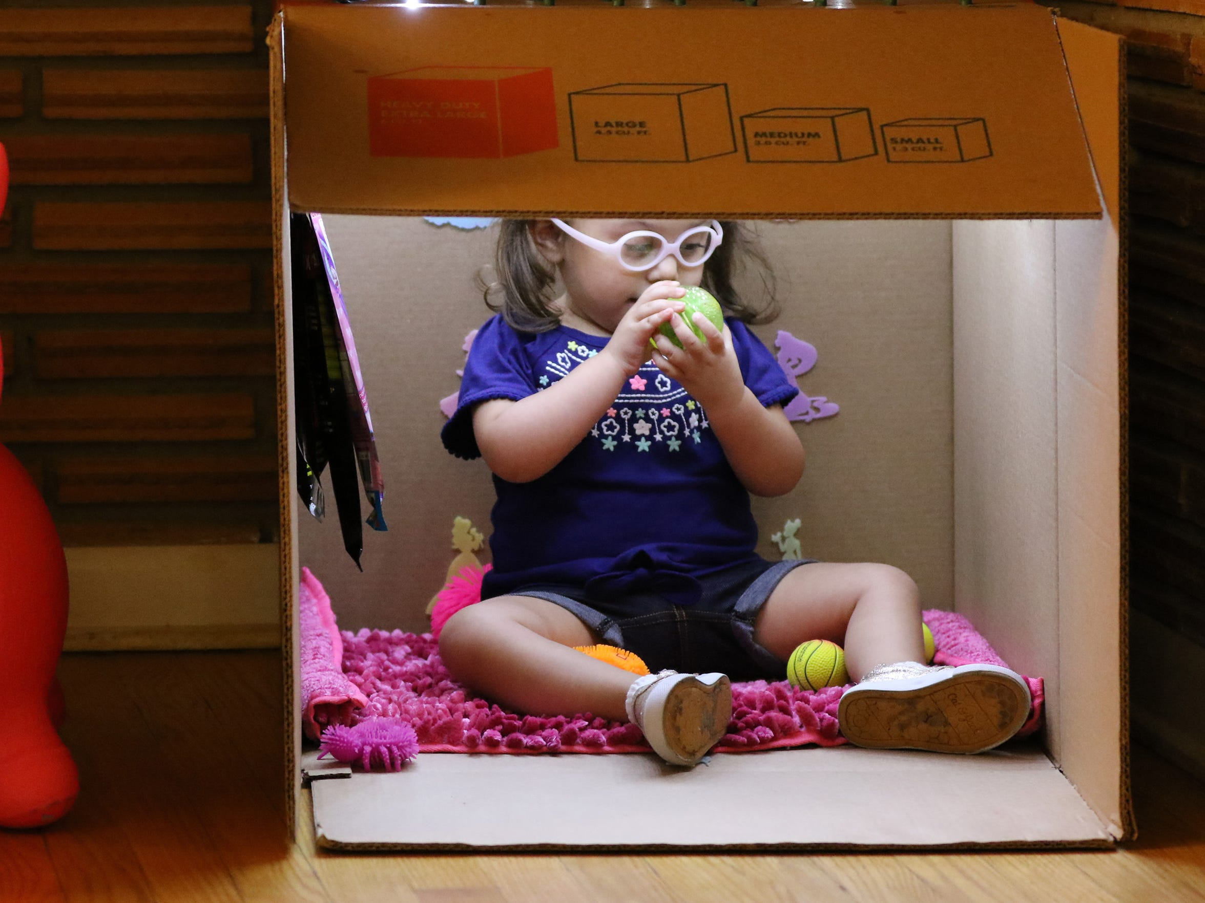 Eleanna Rivas, 3, sits in a lighted cardboard box fort where she likes to hide and be discovered. Eleanna's optic nerves never fully developed; the condition has resulted in limited vision and an off-center focal point.