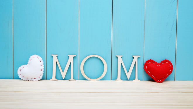 MOM text letters with white and red hearts over blue wooden background