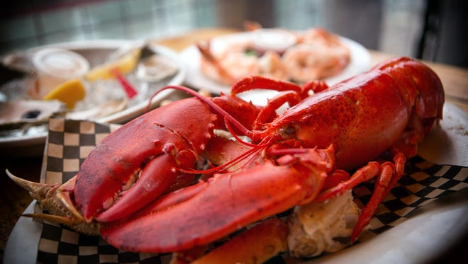 Maine lobster sitting on a bed of crab legs.