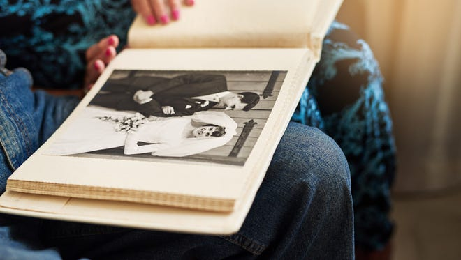 People ooking through a photo album together at home