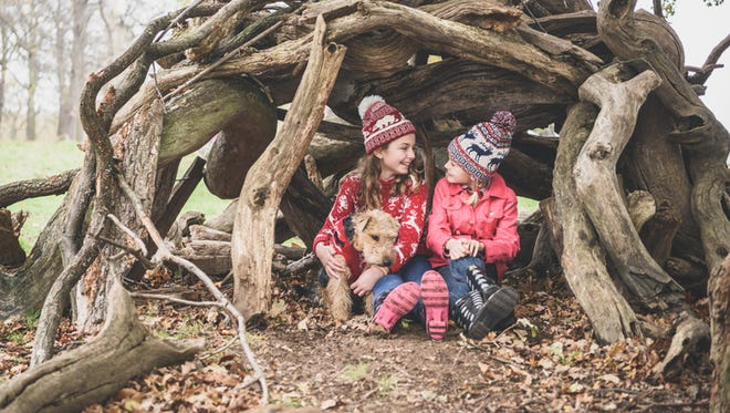 Portrait of two female girls wearing wooly hats hiding in homemade log den