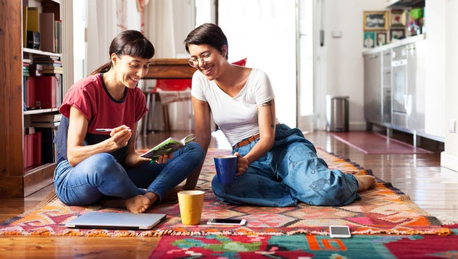 Two women relaxing at home on the floor and enjoying free time