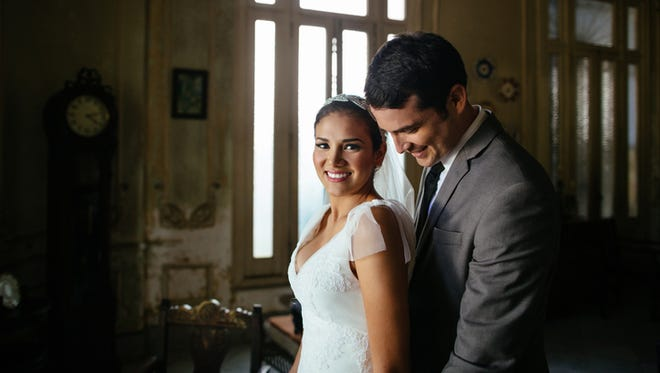 A bride and groom standing together in the living room of an old house.