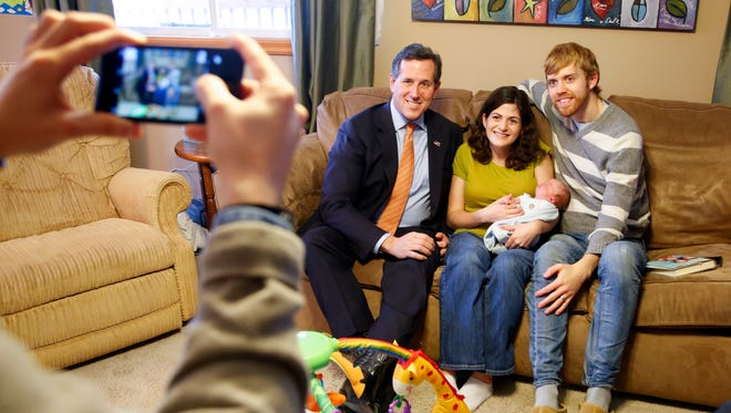 Republican presidential candidate Rick Santorum takes a photo with Katie and Ryan Buck at their in rural Cumming, Iowa Thursday, Jan. 7, 2016.