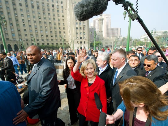 Then-Secretary of State Hillary Clinton (C) waves as