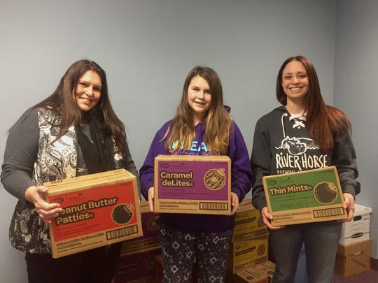 Girl Scout Cassidy Creedon and her mother Karianne Creedon unload cases of Girl Scout cookies with River Horse Brewing's Andrea Whaley.