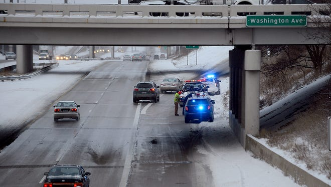 Police and service crews respond to a crash on I-496 westbound at Washington Avenue Friday January 9, 2015. I-496 WB was shutdown for about 40 minutes Friday morning.