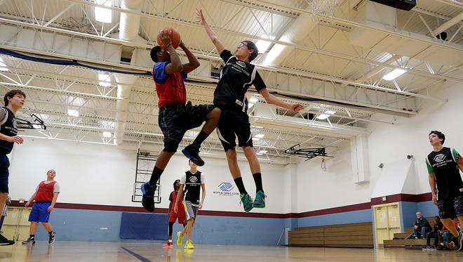 Owen Smits tries to block a shot made by DeShawn Cooper during the BYO5 Christmas Classic Basketball Tournament at the Eastside Boys & Girls Club of Green Bay.