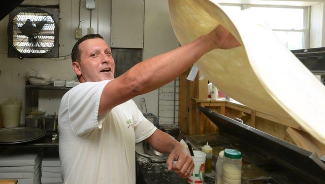 Andy Favilla makes a pizza at Favilla's New York Pizza on Patton Avenue in Asheville.  (John Fletcher 6-20-13)