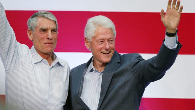Former president Bill Clinton, right, joins U.S. Sen. Mark Udall, D-Colo.,  during a campaign event at a high school in Aurora, Colo., Oct. 27.