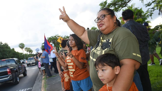 Guam residents wave to motorists during a peace rally at the Chief Kepuha Statue in Hagåtña on Aug. 14, 2017.
