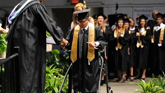 Abilene High graduate Isaac Farias shakes the hand of principal Robert Morrison as he walks across the stage during the Abilene High graduation ceremony on Saturday, May 27, 2017, at the Taylor County Coliseum.