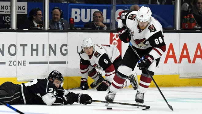 Arizona Coyotes left wing Jamie McGinn (88) and Los Angeles Kings center Trevor Lewis (22) battle for the puck in the second period during a NHL hockey game at the Staples Center, Mar. 14, 2017.