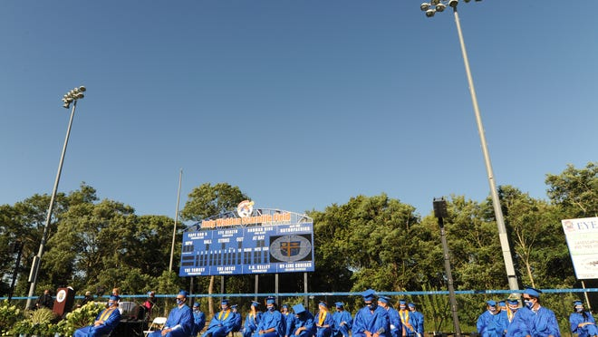 Wearing masks and sitting in rows arranged to maintain social distance, St. John Paul II High School seniors graduate in a ceremony held Monday at the Judy Walden Scarafile Field at McKeon Park. It was the first time the Hyannis school held its graduation outside.