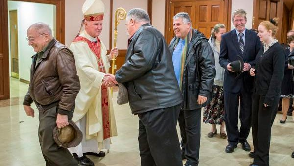 Bishop Francis Malooly greets worshippers following mass at the Immaculate Heart of Mary Church in Wilmington on Monday night