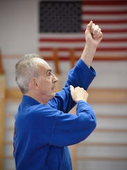 Black belt Ray Dinius works on his karate moves during