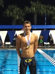 Matthew Limbacher stands on the podium wearing his first place medal after the 2016 state high school swimming meet.