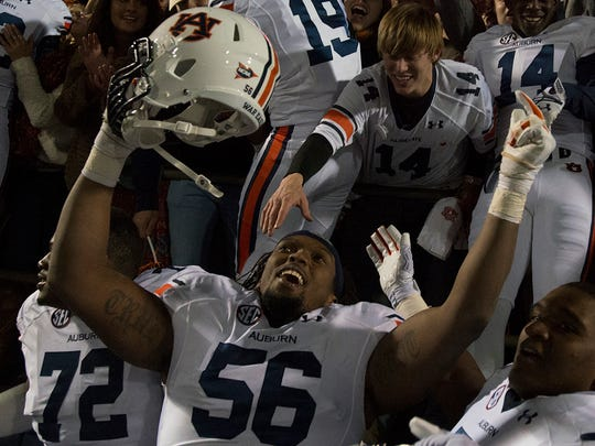 Auburn offensive lineman Avery Young (56) and teammates celebrate with fans after Auburn defeated Ole Miss 35-31 on Saturday.