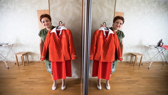 In this photo taken Aug. 3, 2017, Aeroflot flight attendant Yevgeniya Magurina is reflected in a mirror as she shows her uniform during an interview with the Associated Press in Lobnya, outside Moscow.