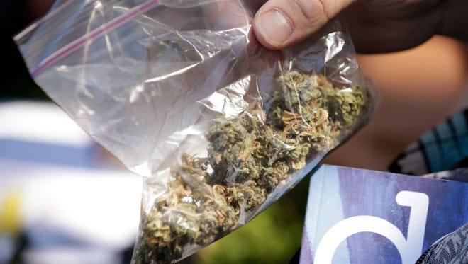 A man pulls out a bag of marijuana to fill a pipe at Hempfest in Seattle in 2013.