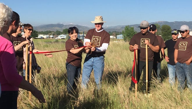 """Kumiko and Craig Lee cut the ribbon on their industrial park Thursday during a groundbreaking ceremony for their project, """"Visions."""""""